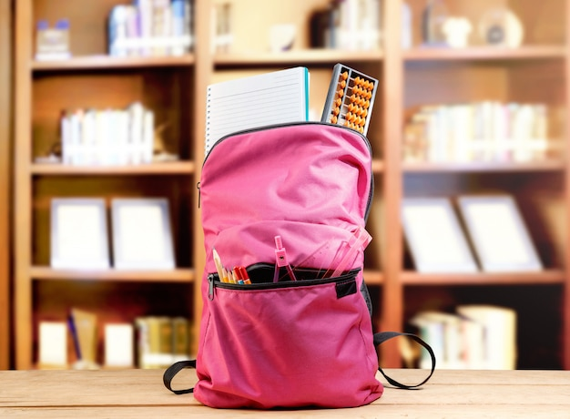 Roze rugzak met boek en verschillende briefpapier op de houten tafel Premium Foto