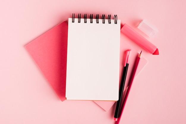 Roze samenstelling met blocnote en bureaulevering op gekleurde oppervlakte Gratis Foto