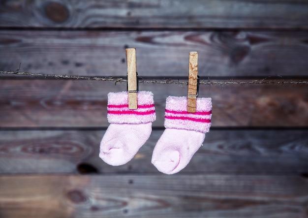 Roze sokken hangen aan de wasknijper houten muur Premium Foto