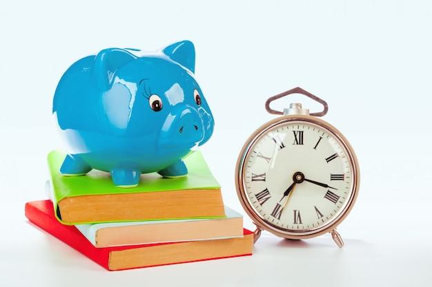 Roze spaarvarken met boeken en wekker Premium Foto