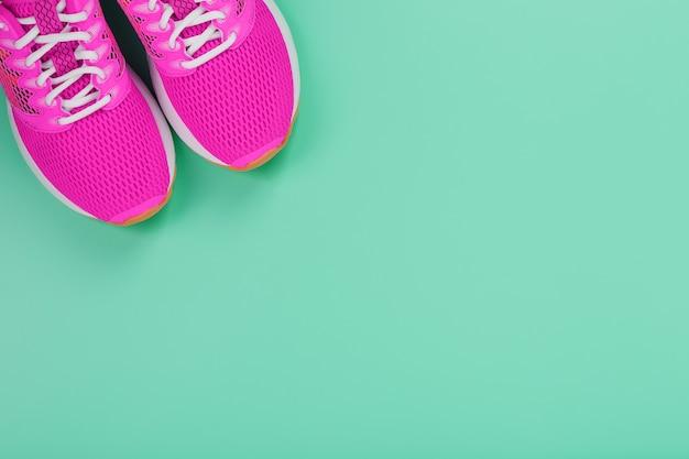 Roze sportschoenen voor hardlopen op een blauwe achtergrond met vrije ruimte. bovenaanzicht, minimalistisch concept Premium Foto