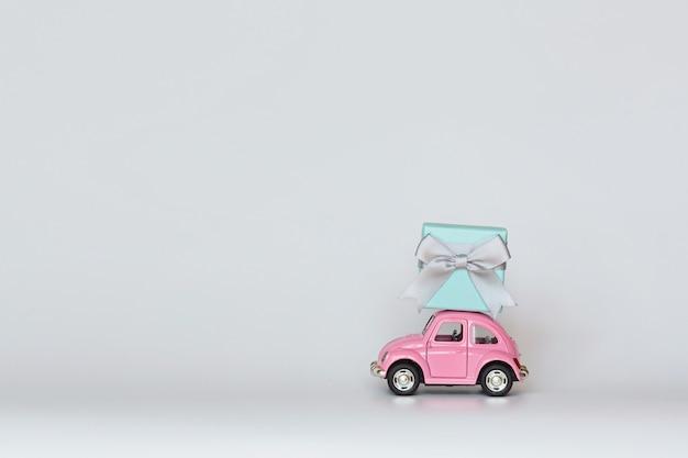Roze stuk speelgoed auto die giftdoos op dak op wit levert Premium Foto