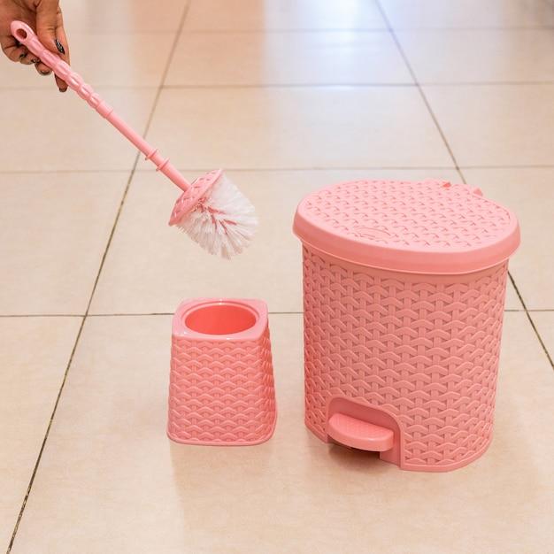 Roze toiletborstel en houder, geïsoleerde vuilnisbak Premium Foto