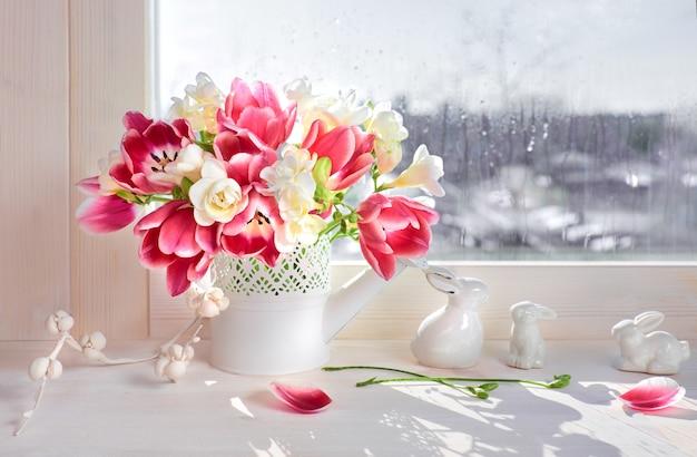 Roze tulpen en witte fresia bloemen met keramiek Premium Foto