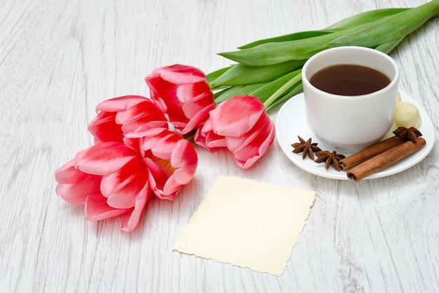 Roze tulpen, mok koffie en cinamon. Premium Foto