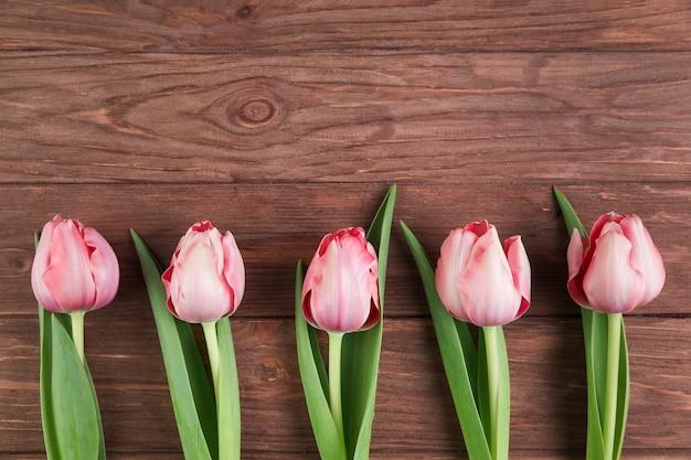 Roze tulpen op houten gestructureerde achtergrond Gratis Foto