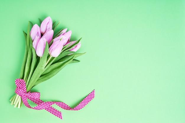 Roze tulpenboeket dat met lint op groene achtergrond wordt verfraaid. Premium Foto