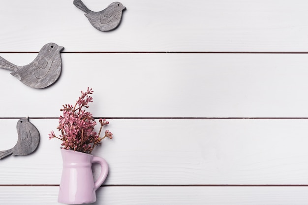 Roze uiterst kleine bloemen in ceramische vaas met houten vogels op wit bureau Gratis Foto