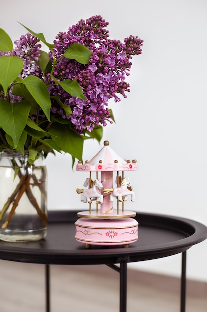 Roze vintage muzikale carrousel en boeket van prachtige lila lentebloemen in vaas op vintage salontafel. Premium Foto