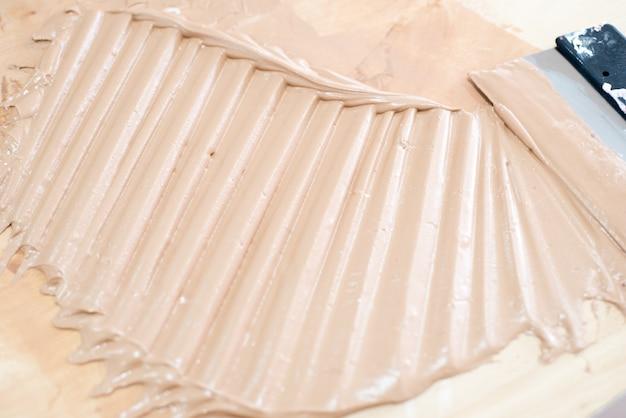 Roze vloeiend gips. troffel applicatie op betonnen muur. stopverf voor wanddecor. ontwerp reparatie Premium Foto