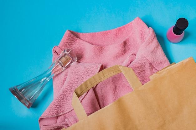 Roze vrouwenblouse, nagellak en parfums in papieren handwerkpakket op blauw. Premium Foto