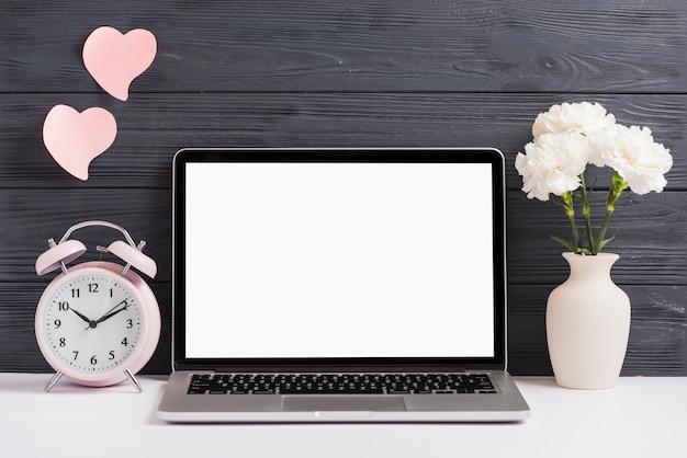 Roze wekker en bloemenvaas op wit bureau tegen houten behang Gratis Foto