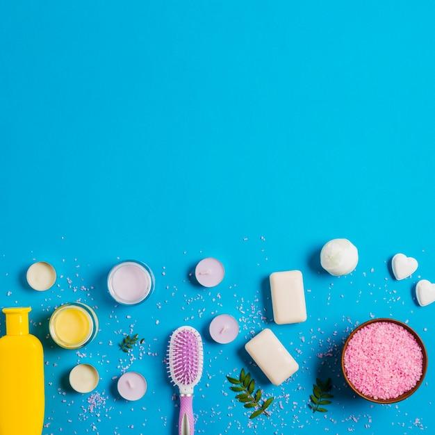 Roze zout; zeep; crème en shampoo met verschillende soorten kaarsen op blauwe achtergrond Gratis Foto