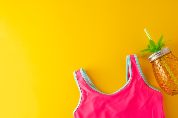 Roze zwempak en ananaspot voor juiuce. zomer achtergrond met kopie ruimte. Premium Foto