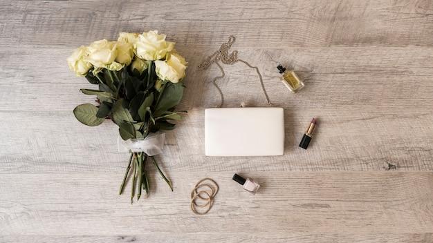 Rozen boeket; koppeling; parfum; lippenstift; nagellak en haarbanden op houten achtergrond Gratis Foto