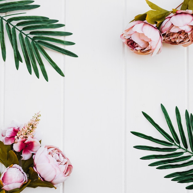 rozen en planten op witte houten achtergrond Gratis Foto