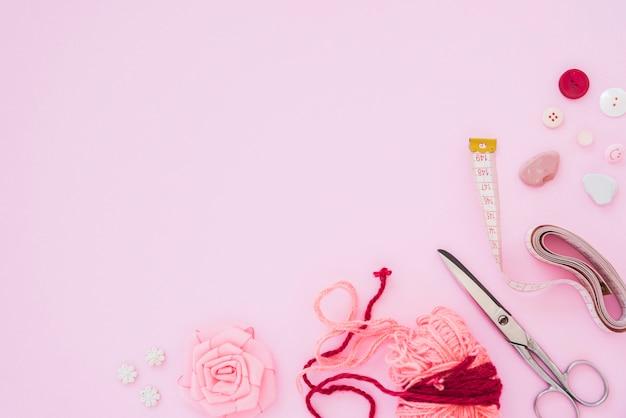 Rozen lint; wol; schaar; meetlint; en knoppen op roze achtergrond met kopie ruimte voor het schrijven van de tekst Gratis Foto