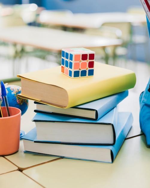 Rubik-kubus op gestapelde boeken op bureau in klaslokaal wordt geplaatst dat Gratis Foto