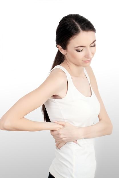 Rugpijn. mooie jonge vrouw gevoel sterke rugpijn, gezondheidsprobleem hebben. aantrekkelijk meisje lijdt aan pijnlijk gevoel, rugpijn, hand in hand op lichaam. gezondheidszorg concept. Premium Foto