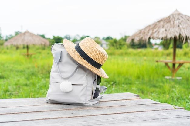 Rugzak met strooien hoed en zonnebril op veld reisconcept Premium Foto