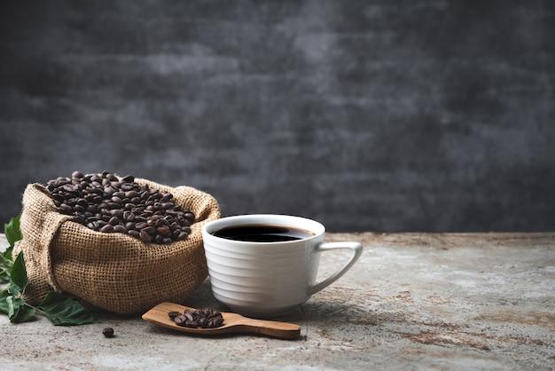 Ruimte zwarte koffie en boon op de achtergrond van het zakvoedsel Premium Foto