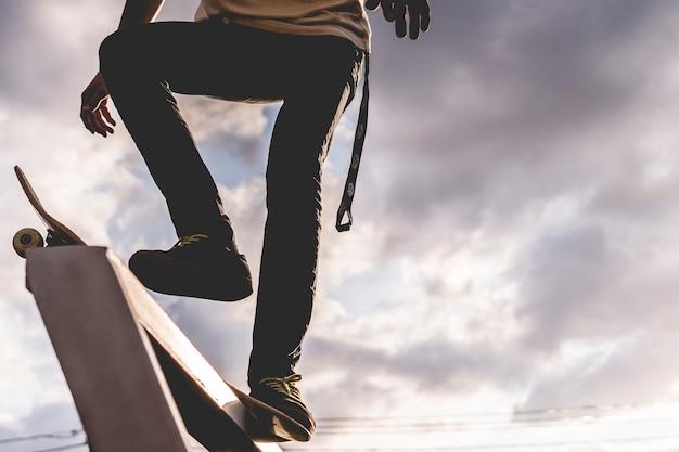 Ruiter die zich op een skateboard vóór de truc tegen hemel bevindt Premium Foto