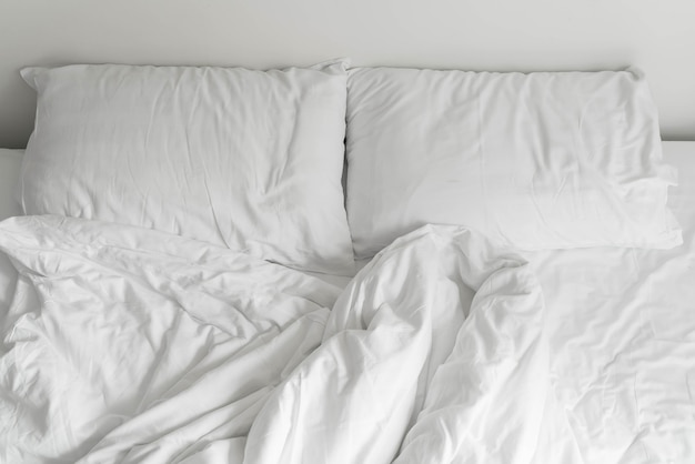 Rumpled bed met witte rommelige kussen decoratie in de slaapkamer ...