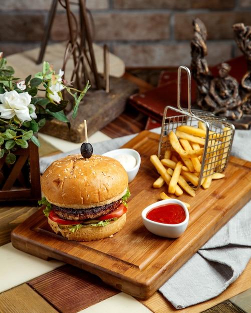 Runderburger geserveerd met frites, ketchup en mayonaise Gratis Foto