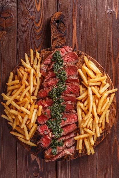 Rundvlees barbecue ribeye steak met chimichurri saus en frietjes. Premium Foto