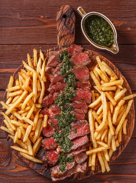 Rundvlees barbecue ribeye steak met chimichurri saus en frietjes. Premium Foto
