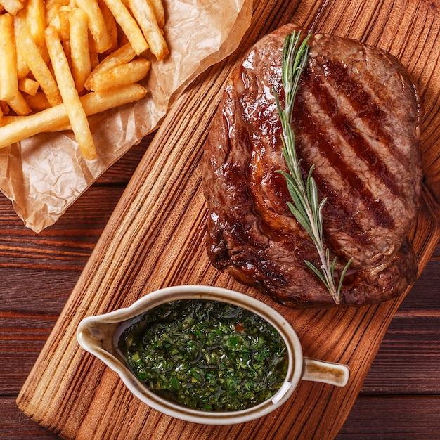 Rundvlees barbecue ribeye steak met chimichurri saus en frietjes Premium Foto
