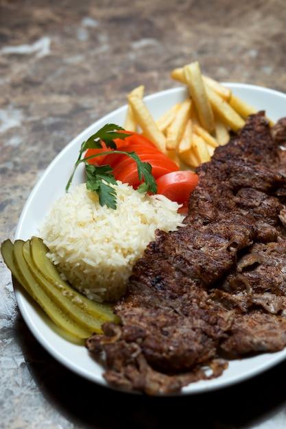 Rundvlees kebab plaat met frietjes, komkommergroenten in het zuur, rijst en tomaat Gratis Foto