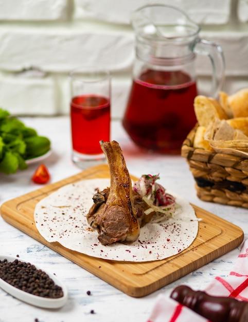 Rundvlees lamskotelet maaltijd in lavash op houten plaat met brood, vegetabels en wijn Gratis Foto