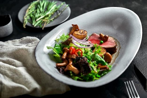 Rundvlees tagliata met groenten. close-up, ingehouden, grijs. Premium Foto