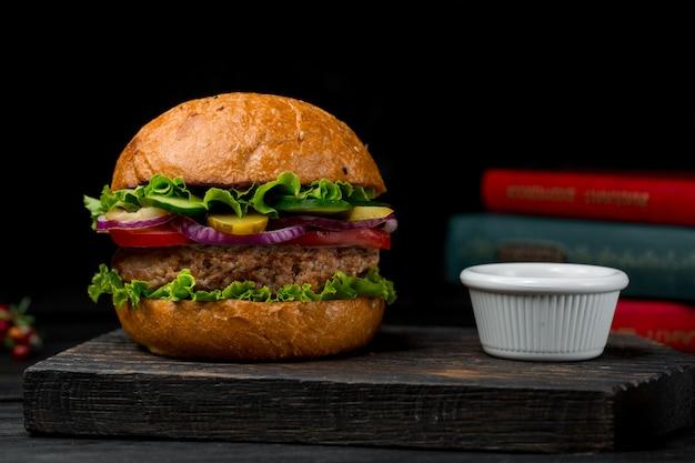 Rundvleeshamburger gevuld met gemengde ingrediënten op een zwart bord Gratis Foto