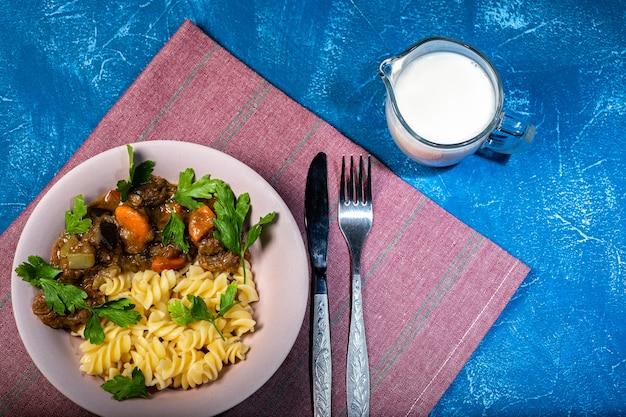 Rundvleeshutspot met groenten en deegwarenspiraal met greens Premium Foto