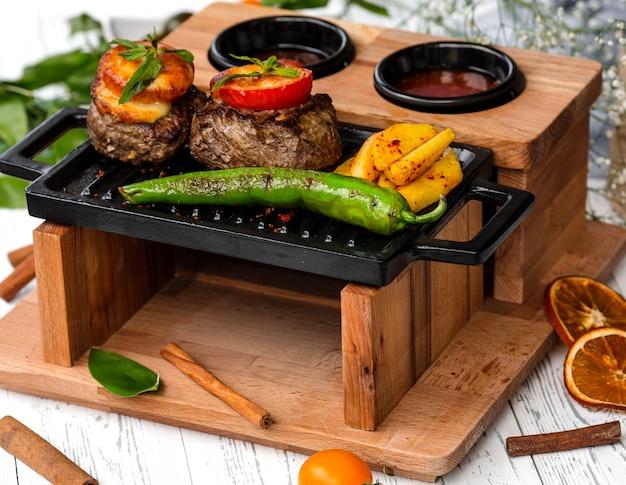 Rundvleeslapjes gegarneerd met tomaat en kaas Gratis Foto