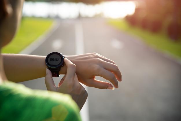 Runner opzetten slimme horloge voordat u tijdens zonsondergang Premium Foto