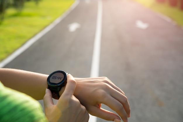 Runner opzetten van slimme horloge voor training tijdens zonsondergang. oefening. Premium Foto