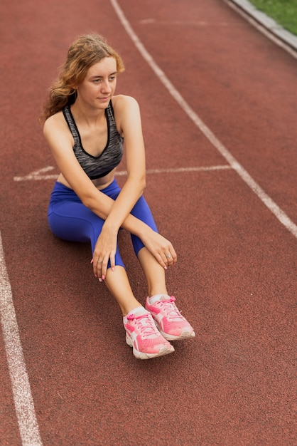 Runner vrouw zitten in het stadion Gratis Foto