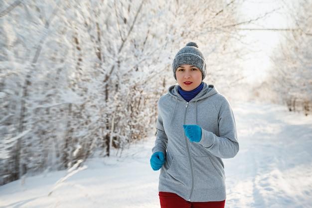 Running sport vrouw. vrouwelijke loper joggen in koude winter woud dragen warme sportieve hardloopkleding en handschoenen. Premium Foto