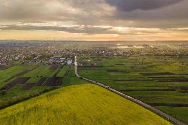 Rurale landschap op lente of zomer dag. luchtfoto van groene, geploegde en bloeiende velden, huisdaken en een weg op zonnige dageraad. drone fotografie. Premium Foto