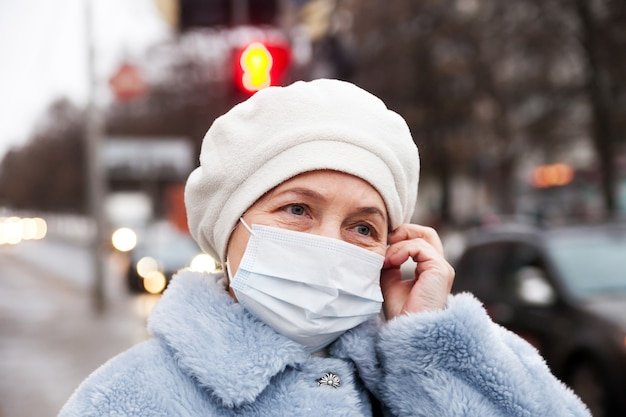 Russische oudere senior vrouw in medische beschermend masker in de winter op straat Premium Foto