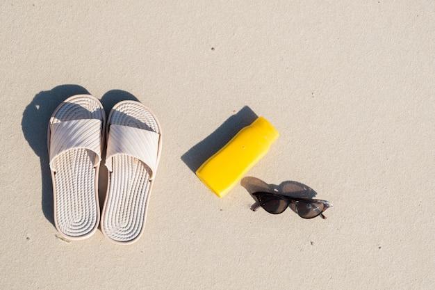 Rust op het strand: slippers, beschermende crème en zonnebril op schoon zand. bovenaanzicht van accessoires voor vakanties aan zee of zomervakantie Premium Foto