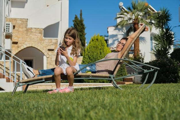 Rustende gelukkige familiemoeder en dochterzitting als openluchtvoorzitter Premium Foto