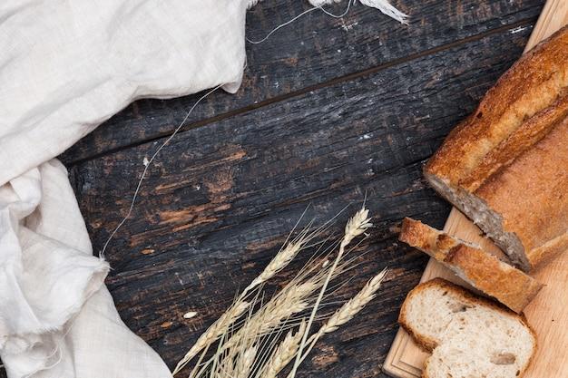 Rustiek brood op houten tafel. donkere bosrijke achtergrond met vrije tekstruimte. Gratis Foto