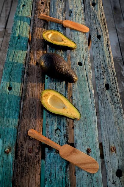 Rustiek houten oppervlak met gesneden en hele avocado's en houten lepels Gratis Foto