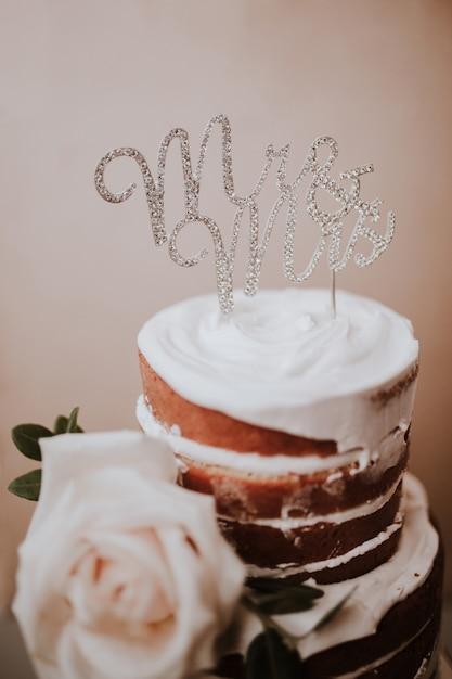 Rustieke bruidstaart met de heer en mevrouw topper op bruine textuur achtergrond Gratis Foto