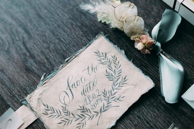Rustieke en grafische kunst van het huwelijk van prachtige kalligrafie kaarten met bloem en chiffon klossen. mooie bruiloft uitnodiging. bovenaanzicht. Premium Foto