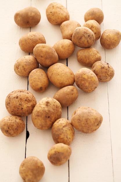 Rustieke ongeschilde aardappelen op een tafel Gratis Foto